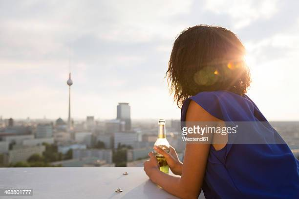 Germany, Berlin, Young woman looking at view, holding beer bottle