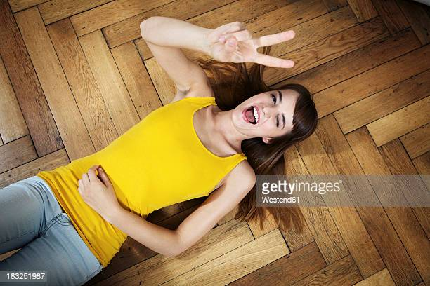Germany, Berlin, Young woman lying on floor and having fun