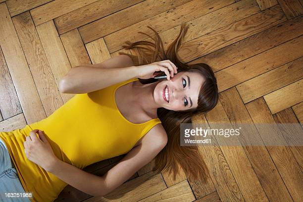 Germany, Berlin, Young woman lying on floor and using smart phone