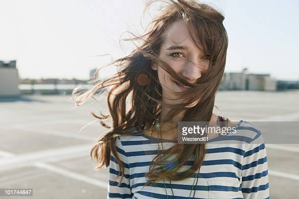 Germany, Berlin, Young woman on parking level, portrait, close-up