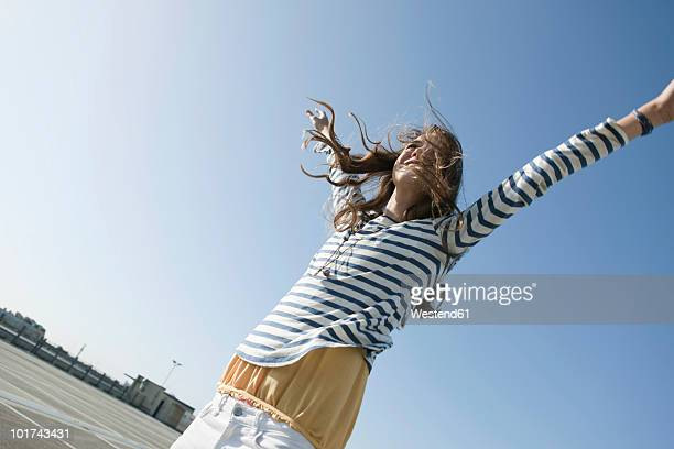 Germany, Berlin, Young woman on parking level, raising arms, smiling, portrait