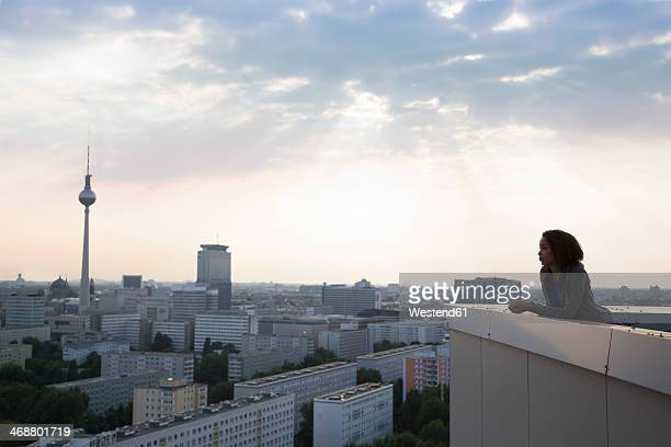 Germany, Berlin, Young woman on rooftop terrace, looking at view