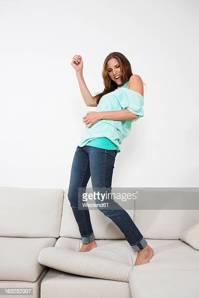 Germany, Berlin, Young woman playing air guitar on couch