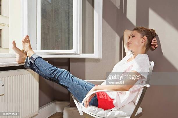 Germany, Berlin, Young woman sitting at open window