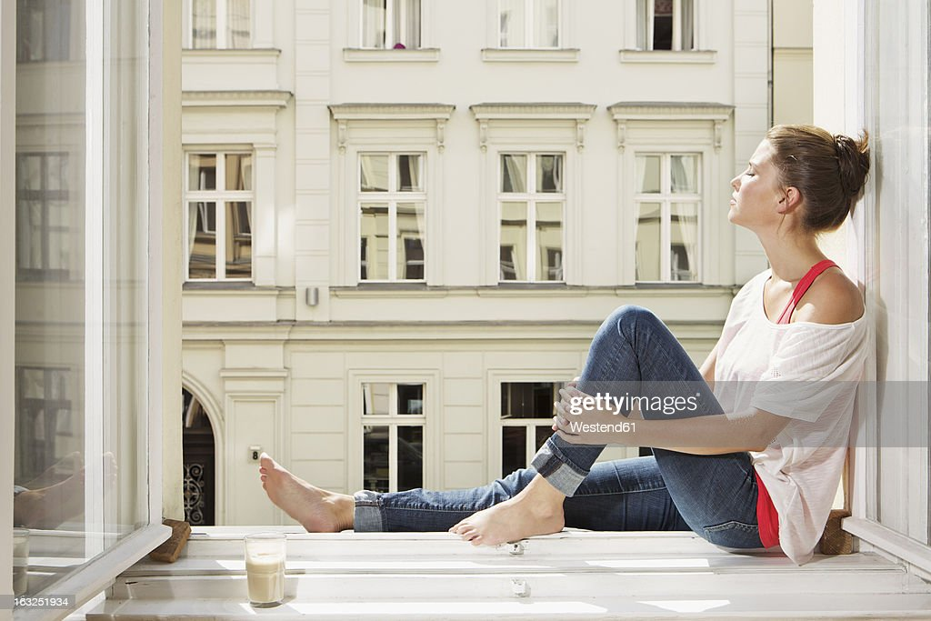 Germany, Berlin, Young woman sitting at open window : Stock-Foto
