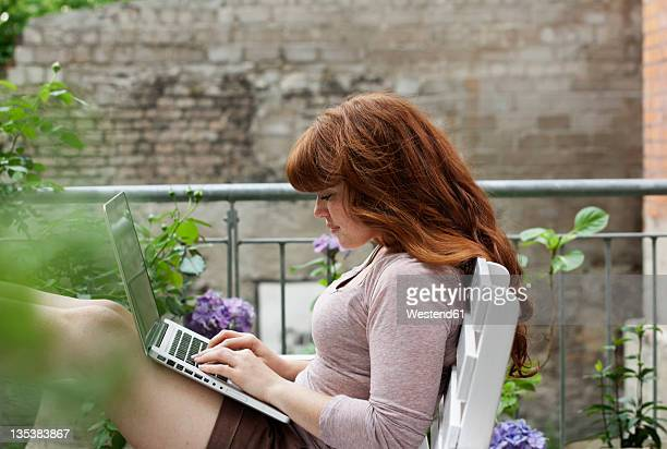 Germany, Berlin, Young woman sitting on bench and using laptop