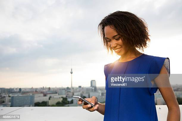 Germany, Berlin, Young woman using mobile phone