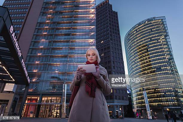 Germany, Berlin, young woman with mini tablet in the evening at Potsdam Square
