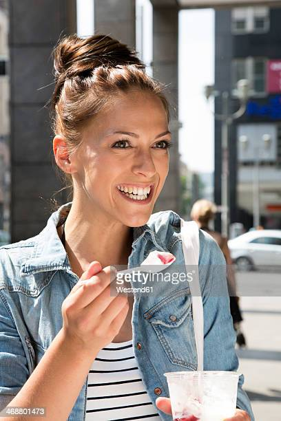 Germany, Berlin, Young women in the city, eating icecream