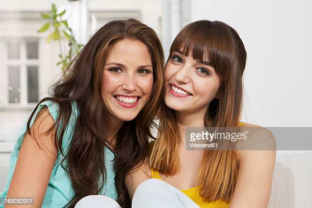 Germany, Berlin, Young women sitting on couch, smiling, portrait