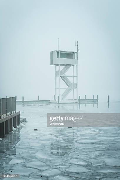 Germany, Berlin-Koepenick, view to frozen Mueggelsee with diving tower in the fog