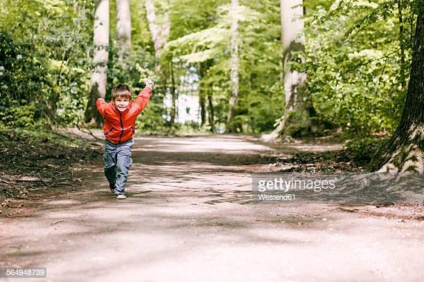 Germany, Bielefeld, boy running on forest path