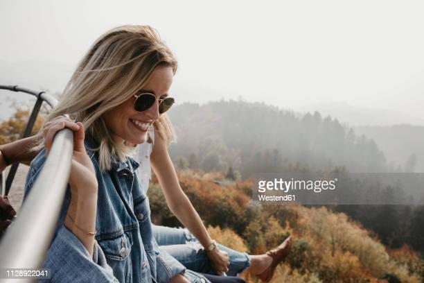 germany, black forest, sitzenkirch, two happy young women sitting at sausenburg castle above mountain forest - weibliche freundschaft stock-fotos und bilder