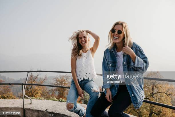 germany, black forest, sitzenkirch, two happy young women sitting on railing at sausenburg castle - istantanea foto e immagini stock
