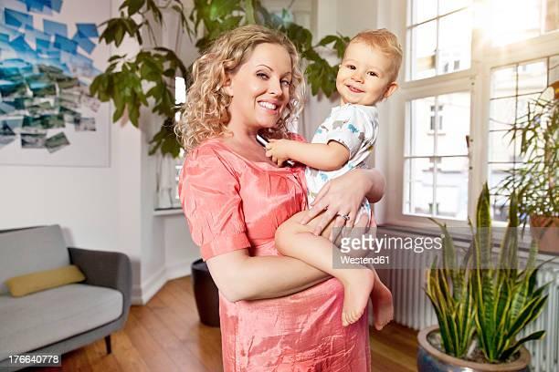 germany, bonn, pregnant mother in living room with her son, smiling, portrait - männliches baby stock-fotos und bilder
