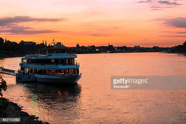 Germany, Bonn, Rhine River with tourboat at sunset