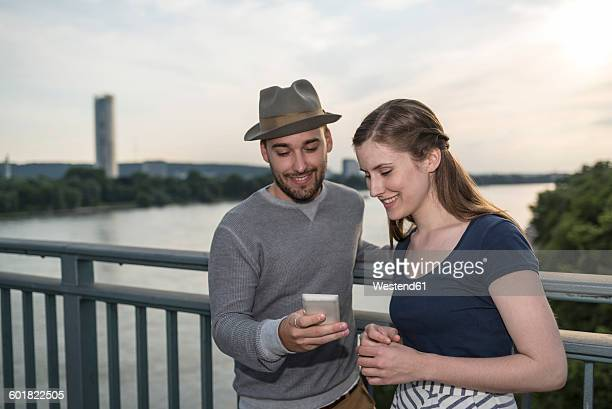 Germany, Bonn, young couple standing on Rhine bridge looking at smartphone