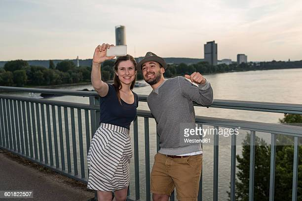Germany, Bonn, young couple standing on Rhine bridge taking a selfie with smartphone
