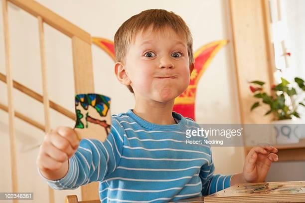 Germany, Boy (4-5) in nursery showing piece of puzzle, portrait