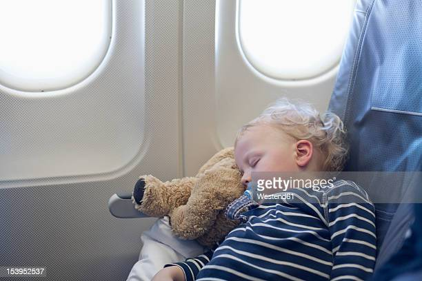 Germany, Boy sleeping in plane