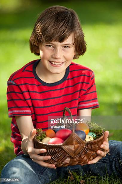 germany, boy (10-11 years) smiling with easter egg basket, portrait - 10 11 years stock pictures, royalty-free photos & images