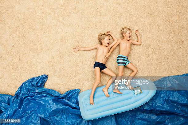 Germany, Boys on inflatable raft in water at beach