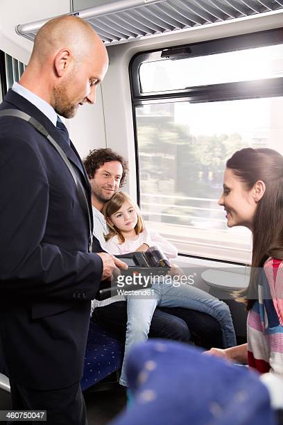 Germany, Brandenburg, Conductor checking tickets of family