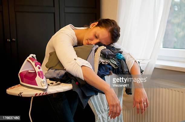 Germany, Brandenburg, Exhausted young woman leaning on ironing board