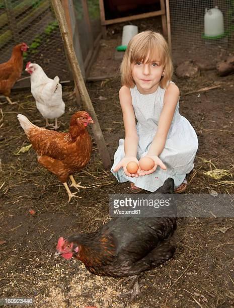 Germany, Brandenburg, Girl holding eggs on hen farm