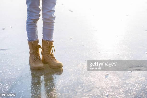 germany, brandenburg, lake straussee, feet with boots on frozen lake - stiefel stock-fotos und bilder