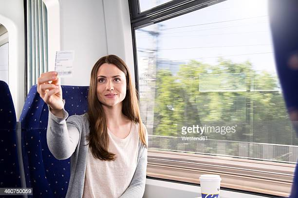 Germany, Brandenburg, Mid adult woman showing ticket, smiling