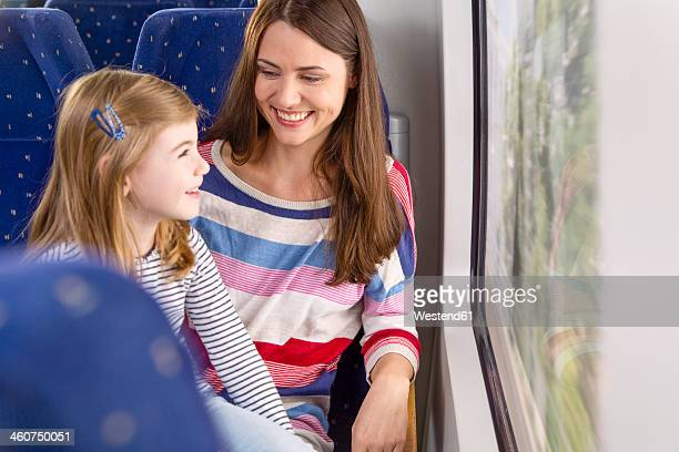 Germany, Brandenburg, Mother with daughter traveling through train