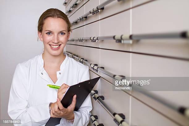Germany, Brandenburg, Pharmacist with clip board, smiling, portrait