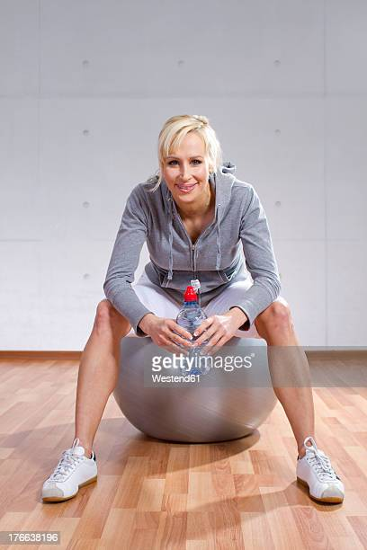 Germany, Brandenburg, Portrait of woman sitting on fitness ball in gym, smiling