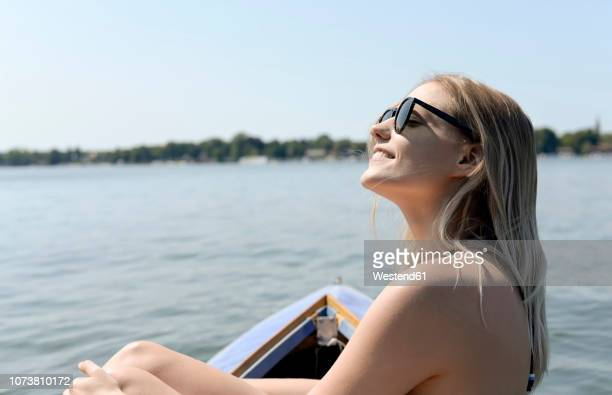 germany, brandenburg, smiling blond woman sunbathing on zeuthener see - one young woman only stock pictures, royalty-free photos & images