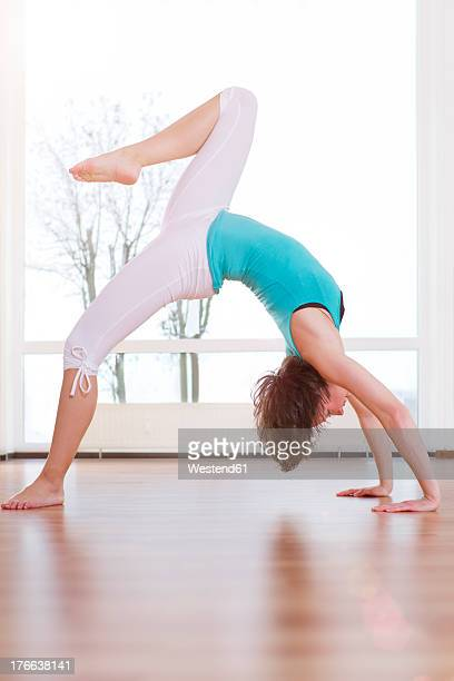 Germany, Brandenburg, Young woman exercising in gym