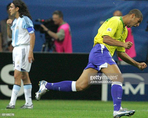 Brazilian forward Adriano celebrates after scoring the opening goal as Argentine defender and captain Juan Pablo Sorin reacts during the 2005 FIFA...