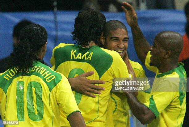 Brazilian forward Adriano is congratulated by midfielder Kaka and midfielder Ze Roberto captain Ronaldinho after scoring the opening during the 2005...