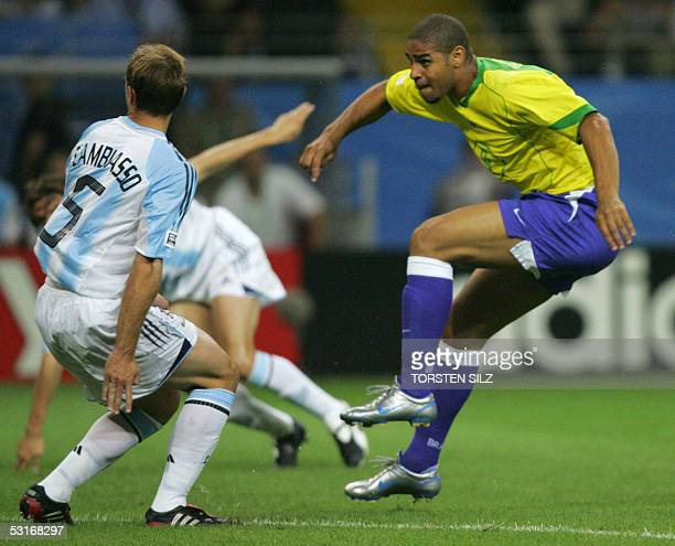 Brazilian forward Adriano scores the opening goal past Argentine midfielder Esteban Cambiasso during the 2005 FIFA Confederations Cup football final...