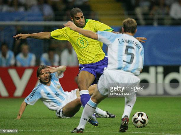 Brazilian forward Adriano scores the opening goal past Argentine midfielder Esteban Cambiasso and defender Gabriel Heinze during the 2005 FIFA...