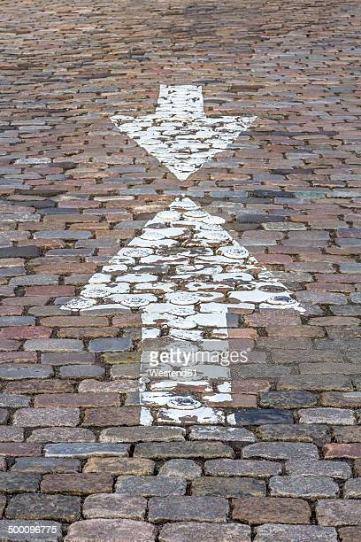 Germany, Bremen, Opposing arrow signs on cobblestone pavement