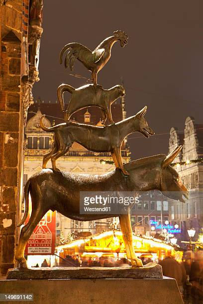 Germany, Bremen, Statue of Bremen City Minstrels in front of Christmas market at night