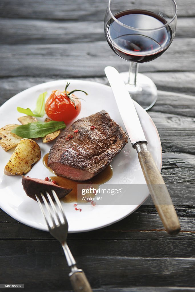 Germany, Bremen, Steak with vegetable and wine on table : Stock Photo
