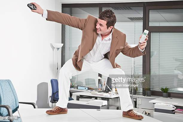Germany, Business man standing on desk, holding phone and mouse