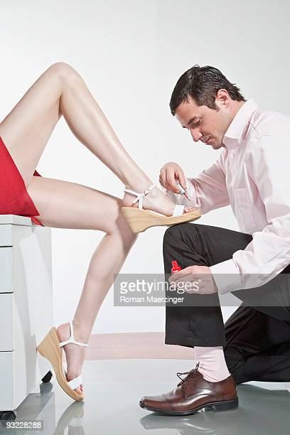 germany, business people in office, man painting woman's toenails - women dominating men stock photos and pictures
