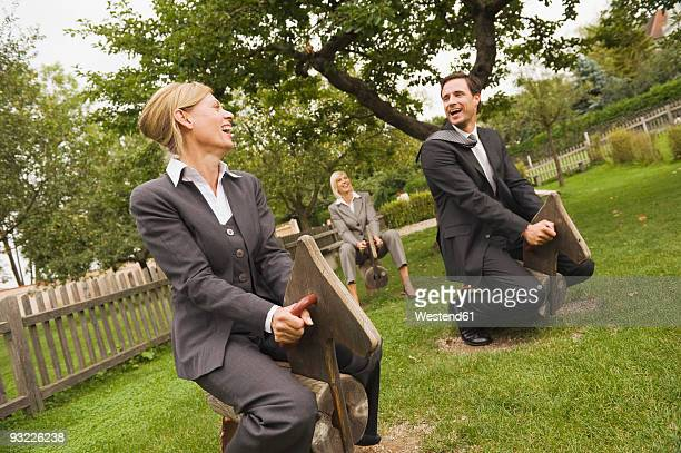 Germany, Businessman and woman sitting on rocking horse, laughing