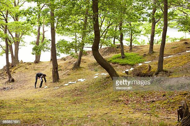 Germany, businessman picking up sheets of paper from forest soil