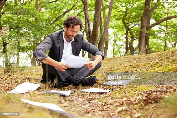 Germany, businessman sitting in forest reading documents