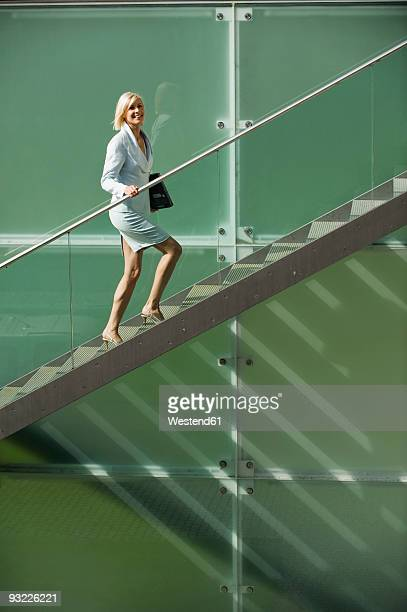 Germany, Businesswoman walking up stairs, smiling