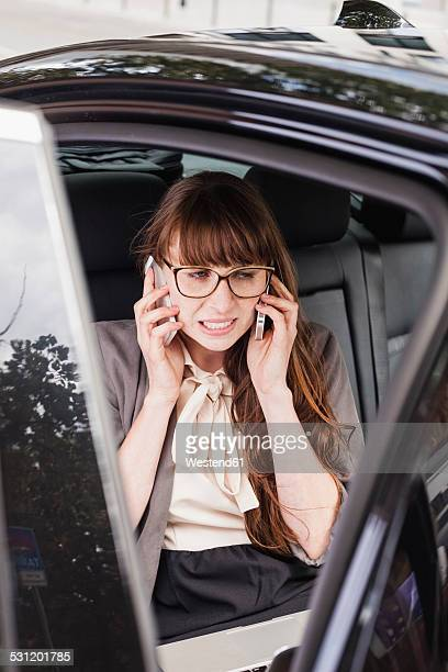 Germany, businesswoman sitting in a car using two smartphones